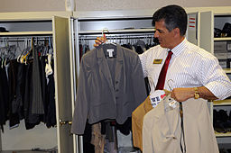 Man picking clothes out of his closet