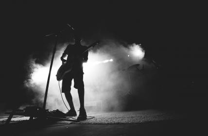 man holding guitar at microphone with fog mist in background