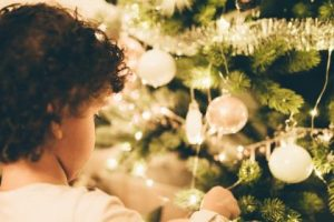 girl putting ornament on christmas tree
